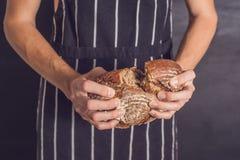 Piekarniany mężczyzna trzyma domowej roboty nieociosanego pszenicznego chleb w rękach Selectiv zdjęcia royalty free