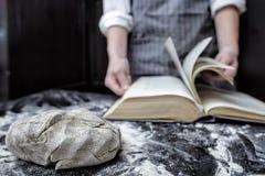 Piekarniany szef kuchni patrzeje dla przepisu w książce kucharska Fotografia Stock