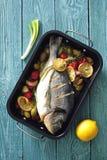 Piekarnik piec całej dennej ryba z zielonymi oliwkami, czereśniowymi pomidorami, cytryną i zielarskim masłem, zdjęcia stock