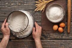 Piekarz odsiewa mąkę na ciemnym nieociosanym drewnianym tle Fotografia Royalty Free