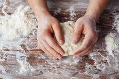 Piekarz przygotowywa ciasto na drewnianym stole, męskie ręki ugniata ciasto z mąką zdjęcie royalty free