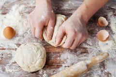Piekarz przygotowywa ciasto na drewnianym stole, męskie ręki ugniata ciasto z mąką fotografia stock
