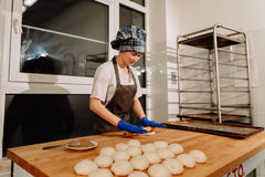 Piekarz robi cynamonowym rolkom Zdjęcia Stock