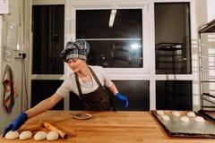 Piekarz robi cynamonowym rolkom Zdjęcie Stock