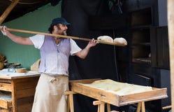 Piekarz stawia chleb na łopacie w piekarnika Zdjęcie Royalty Free