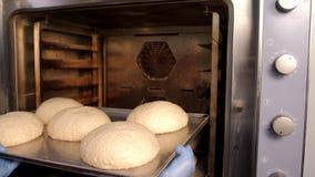 Piekarz stawia chleb w piekarniku zbiory