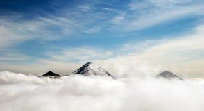 Pieken van bergen boven de wolken Stock Fotografie