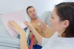 Pielęgniarka analizuje kierowego monitoru wydruk zdjęcia stock