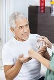 Pielęgniarka Daje medycynie I Wodnemu szkłu pacjent Zdjęcie Stock