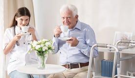 Pielęgniarka i pacjent pije herbaty fotografia royalty free