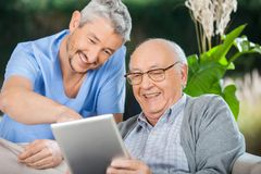Pielęgniarka I Starszy mężczyzna Cieszy się Podczas gdy Używać pastylkę Fotografia Stock