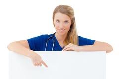 Pielęgniarka, lekarka pokazuje puste miejsce deski znaka/. Obrazy Royalty Free