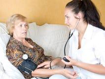 Pielęgniarka mierzy ciśnienie krwi starsza kobieta fotografia stock