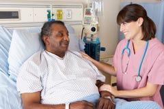 Pielęgniarka Opowiada Starszy Męski pacjent Na oddziale Zdjęcia Royalty Free