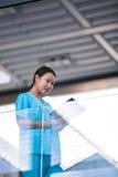 Pielęgniarka patrzeje jej dzienniczek zdjęcie stock