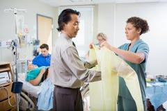 Pielęgniarka Pomaga lekarkę W Być ubranym operaci togę Obrazy Royalty Free
