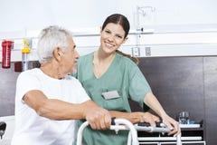 Pielęgniarka Pomaga Starszego mężczyzna Używać piechura Przy Rehab centrum obraz royalty free