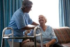 Pielęgniarka pomaga starszej kobiety w pozyci zdjęcia royalty free