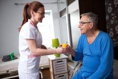 Pielęgniarka przy karmiącym domem przynosi sok pomarańczowego starzy pacjenci zdjęcia stock