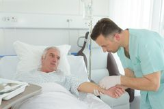 Pielęgniarka robi wtryskowego starszego pacjenta na łóżku szpitalnym Fotografia Stock