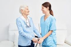 Pielęgniarka wspiera starszej kobiety z odprowadzenie ramą fotografia royalty free
