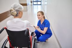 Pielęgniarka z starszą kobietą w wózku inwalidzkim przy szpitalem Fotografia Royalty Free