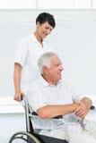 Pielęgniarka z starszym cierpliwym obsiadaniem w wózku inwalidzkim fotografia stock