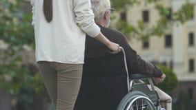 Pielęgniarki dosunięcia mężczyzna w wózku inwalidzkim, warunek życiowy dla niepełnosprawni w mieście zdjęcie wideo