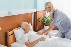 pielęgniarki i seniora kobieta uśmiecha się each inny w pielęgnaci obraz royalty free