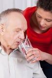 Pielęgniarki pomagać obezwładniający z wodą pitną Obraz Stock
