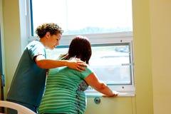Pielęgniarki uspokajająca mama w pracie Zdjęcia Royalty Free