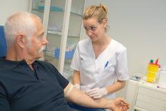 Pielęgniarki znalezienia pacjentów żyła dla badania krwi fotografia royalty free