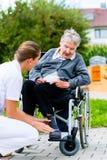 Pielęgnuje dosunięcie starszej kobiety w wózku inwalidzkim na spacerze zdjęcie royalty free