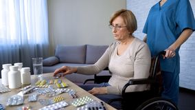 Pielęgnuje dowiezienie starszej damy w wózku inwalidzkim stół dla brać medycynę, traktowanie fotografia stock