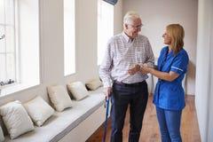 Pielęgnuje pomaga starszego mężczyzna chodzić używać chodzącego kij zdjęcie royalty free