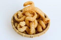 Piel curruscante del cerdo, comida tailandesa del estilo en una cesta de mimbre foto de archivo