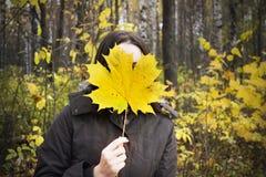 Piel de la muchacha la cara con la hoja de mármol amarilla enorme en bosque del otoño Foto de archivo
