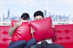 Piel de los pares detrás de la almohada en el sofá rojo Imagen de archivo libre de regalías