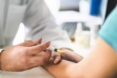 Pielęgniarka i cierpliwy bierze badanie krwi w doktorskim biurowym pokoju w szpitalu zdjęcie stock