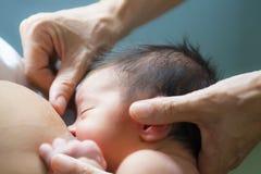 Pielęgnuje heps matka breastfeeding jej nowonarodzonego dziecka Obraz Royalty Free