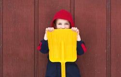 Pieles jovenes del muchacho detrás de la pala del juguete Imagenes de archivo