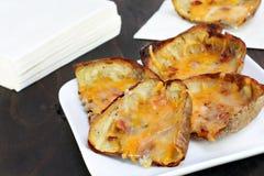 Pieles y queso cocidos al horno de patata Fotos de archivo libres de regalías