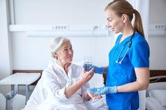 Pielęgnuje dawać medycynie starsza kobieta przy szpitalem Obraz Stock