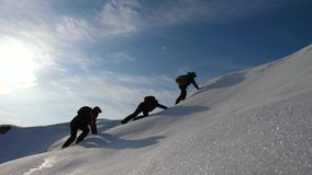 Pielgrzymi wspinają się śnieżną górę w Alaska coordinated pracy zespołowej mountaineering w zimy turystyce w północy Drużyna zbiory