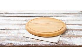 Pielucha i deska dla pizzy na drewnianym biurku Sterta kolorowi naczynie ręczniki na białym drewnianym stołowym tło odgórnego wid obraz royalty free