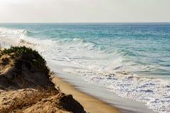 Pieniąca fading fala na piaskowatej linii brzegowej, falowy cresting, pieniący backwash, piaskowaty faleza wzrost zdjęcia stock