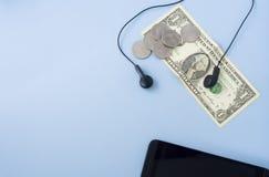 Pieniądze banknot, monety z czarną słuchawki i czarny telefon komórkowy, zdjęcie royalty free