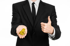 Pieniądze i biznesu temat: mężczyzna trzyma stos odizolowywający złociste monety w studiu na białym tle w czarnym kostiumu Obrazy Royalty Free