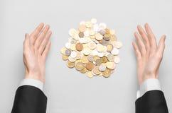 Pieniądze i biznesu temat: ręki w czarnym kostiumu wskazują stos złociste monety na białym stole w studiu Zdjęcie Royalty Free