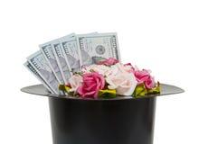 Pieniądze i kwiaty w czarnej magii kapeluszu odizolowywającym na białym backgro Fotografia Stock